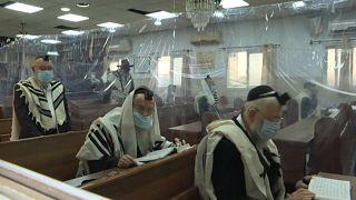 يهود متدينون يؤدون الصلاة مع احترام القيود التي فرضتها جائحة كورونا. المكان بلدة بني براك في إسرائيل