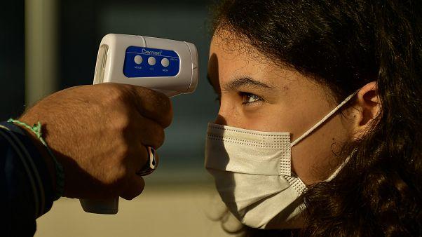 مراقبة درجة حرارة جسم تلميذة قبل دخولها القسم وهي ترتدي كمامة وقاية من فيروس كورونا.