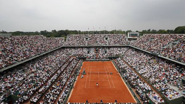 In this June 10, 2018 file photo, the crowd watch Austria's Dominic Thiem serving to Spain's Rafael Nadal during the men's final match of the French Open.