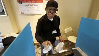 متطوع يطهر شاشة آلة تضويت إلكترونية وسط مخاوف من فيروس في مركز اقتراع في شيكاغو. 2020/03/17