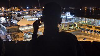 Un senzatetto marocchino guarda il porto di Melilla in una sera di settembre del 2018 - Foto d'archivio