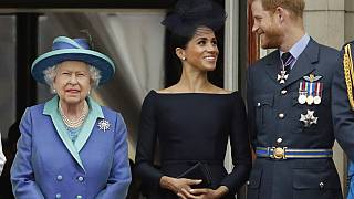 Britain's Queen Elizabeth II, Meghan and Harry watch a flypast of Royal Air Force aircraft pass over Buckingham Palace in London