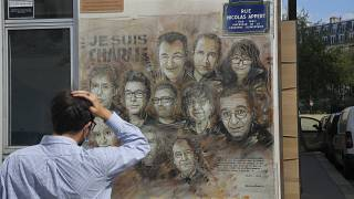 A man looks at a painting in tribute to the members of the Charlie Hebdo attack. Paris, France. Sept 2, 2020.