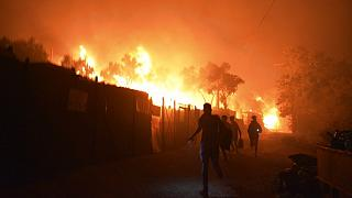 Refugees and migrants run as fire burns in the Moria refugee camp on the northeastern Aegean island of Lesbos, Greece, on Wednesday, Sept. 9, 2020.