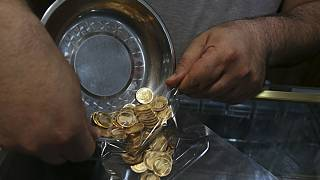 Iranian goldsmith counts gold coins in the sprawling Grand Bazaar