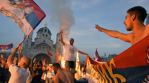 Opposition supporters celebrate after the parliamentary elections in front of the Serbian Orthodox Church of Christ's Resurrection in Podgorica, Montenegro, Monday, Aug. 31