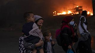 Migrants flee from the Moria refugee camp during a second fire, on the northeastern Aegean island of Lesbos, Greece, on Wednesday, Sept. 9, 2020. F