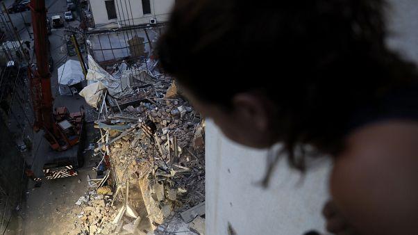 Una joven libanesa observa desde su casa los destrozos tras la explosión en Beirut