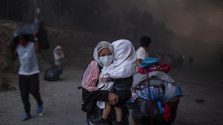 Migranten verlassen brennendes Camp Moria.