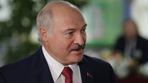 Belarusian President Alexander Lukashenko smiles after voting at a polling station during parliamentary elections, in Minsk, Belarus