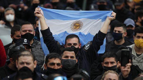 Un policía bonaerense alza una bandera de Argentina durante las protestas