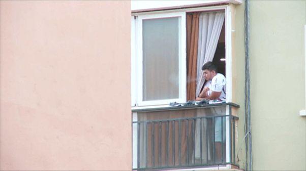 Un joven fuma un cigarro en el balcón de su casa en uno de los barrios que ha entrado en cuarentena