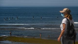 A woman wearing a face mask walks past paddle surfers riding waves at Parede beach in Cascais in the outskirts of Lisbon