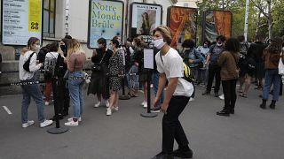 Un joven pasa en monopatín ante la gente que hace cola ante el Palacio de Tokio en París