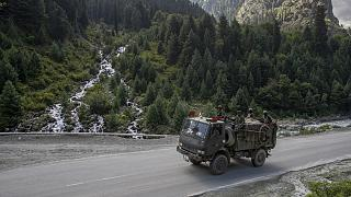 Indian army soldiers keep guard on top of their vehicle as their convoy moves on the Srinagar- Ladakh highway at Gagangeer, northeast of Srinagar, Indian-controlled Kashmir.