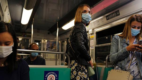Women stand in a suburb Paris metro train wearing a protective face mask as a precaution against the coronavirus in Paris, Saturday, Sept. 5, 2020.
