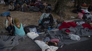 مهاجرون ينامون على الطريق بالقرب من مخيم موريا للاجئين في اليونان.