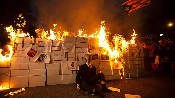 Pro-independent supporters set an effigy representing King Felipe VI on fire during the Catalan National Day in Barcelona,
