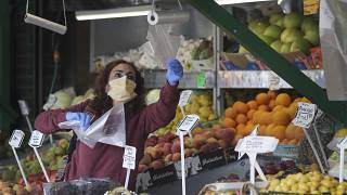 FILE: a woman wears a face mask to protect against the coronavirus as she shops at a fruit and vegetable shop in London, April 29, 2020.