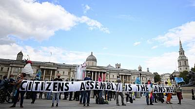 """Activists from the climate protest group Extinction Rebellion hold up a banner displaying """"Citizens' Assembly is the Answer' in Trafalgar Square in central London."""