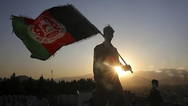 a man waves an Afghan flag during Independence Day celebrations in Kabul, Afghanistan.