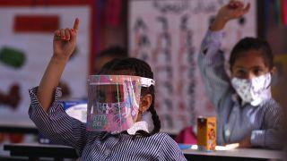 طلاب المدارس الابتدائية الفلسطينيون يرتدون أقنعة واقية للوجه في الفصل الدراسي وسط جائحة فيروس كورونا