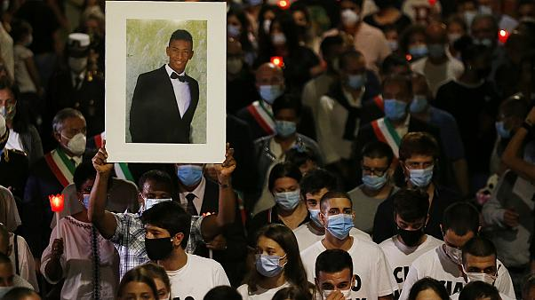 A man holds up a picture of Willy Monteiro Duarte during a torch light procession in Paliano, Italy, on September 9, 2020