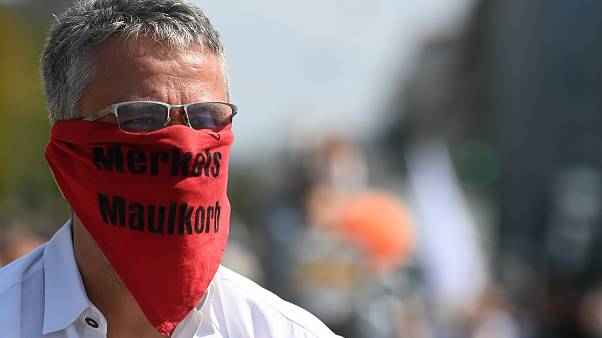 A participant at a demonstration against COVID-19 restrictions wears a scarf reading 'Merkel's muzzle', Munich, Germany. September 12, 2020.