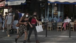 People, wearing a protective face mask as a precaution against the coronavirus, walk in Paris, Thursday Sept. 10, 2020.