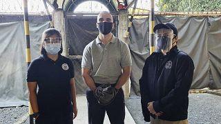 الجندي الامريكي المعفو عنه يتوسط رجلي أمن في مكتب الهجرة في الفلبين