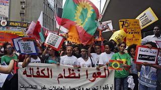 """عاملات منازل مهاجرات يحملن لافتة باللغة العربية كتب عليها """"ألغوا نظام الكفالة""""، خلال تجمع  للاحتفال باليوم العالمي للعمال"""