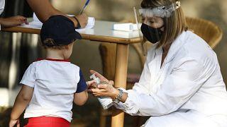 Νοσηλεύτρια βάζει αντισηπτικό στο χεράκι παιδιού στην Ιταλία