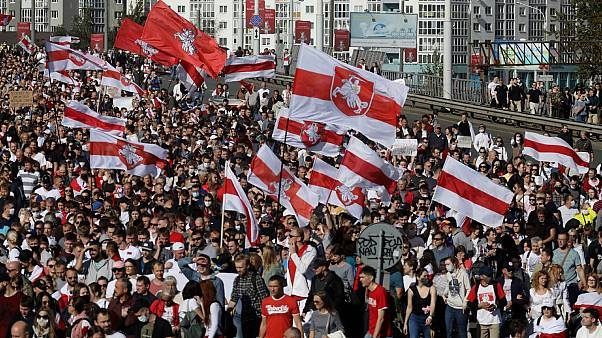 Protesters with old Belarusian national flags march during an opposition supporters' rally protesting election results in Minsk, Belarus. September 13, 2020.