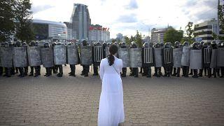 Женщина в белом платье перед шеренгой силовиков в Минске