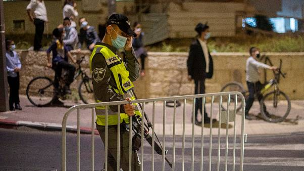 In this Tuesday, Sept. 8, 2020 file photo, an Israeli border policeman sets up a barrier during an overnight curfew amid the coronavirus pandemic, Beit Shemes, Israel.