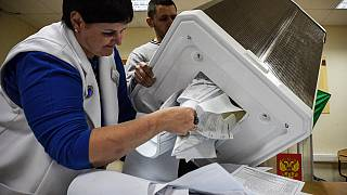 Members of a local electoral commission empty a ballot box at a polling station in Siberian city of Novosibirsk, on September 13, 2020.