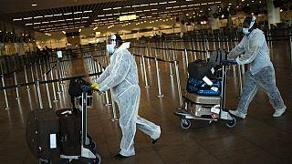 Pasajeros con equipamiento de protección personal completo en el aeropuerto Zaventem de Bruselas