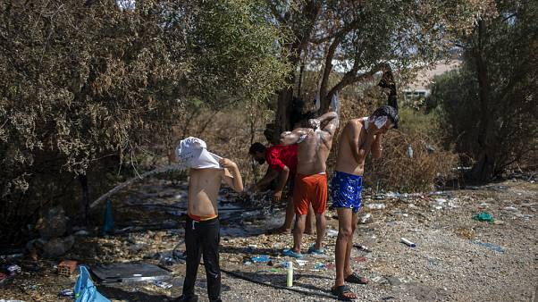 Migrants and refugees wash in a field near the burned Moria camp on island of Lesbos, Greece