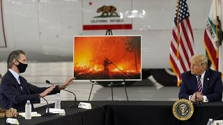 President Donald Trump listens as California Gov. Gavin Newsom speaks during a briefing at Sacramento McClellan Airport, California, Sept. 14, 2020, on western wildfires.