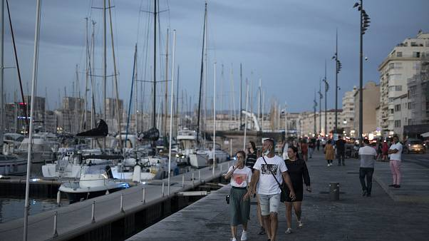 People stroll along Marseille's Old Port, southern France, July 25, 2020. Marseille and Bordeaux are tightening restrictions amid a sharp uptick in coronavirus cases.