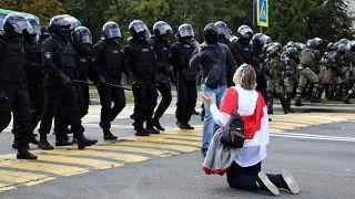 Eine Frau kniet vor Polizeikräften in Minsk während der Proteste