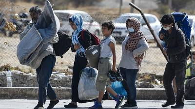 A family carrying their belongings walk toward a new temporary camp, set up to shelter refugees from the burnt Moria refugee camp, on the island of Lesbos