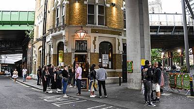 People sit and drink, outside a pub at Borough Market, as the capital is set to reopen after the lockdown due to the coronavirus outbreak, in London, Saturday, July 4, 2020.