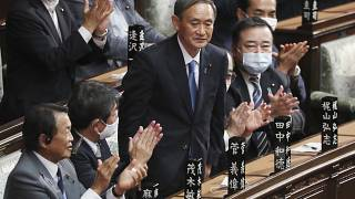 Yoshihide Suga stands up after being elected as Japan's new prime minister at parliament's lower house in Tokyo, Wednesday, Sept. 16, 2020.