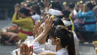 Women wearing face masks as a precaution against the new coronavirus outbreak pray during a Hindu ritual prayer at a temple in Bali, Indonesia