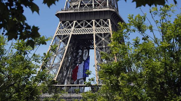 The French national flag decorates the Eiffel Tower