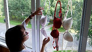سيدة تعلق حمالات الصدر الحمراء والبيضاء في النافذة