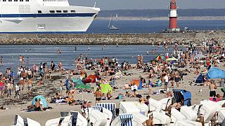 People enjoy the unusually warm late summer weather on the Baltic Sea beach  in Warnemuende, Germany
