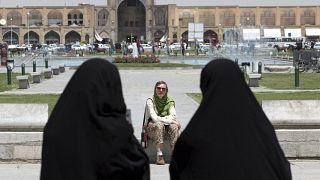 İran'ın İsfahan kentinde bir yabancı turistin önünden geçen çarşaflı İranlı kadınlar (arşiv)