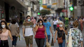 Personas con mascarilla caminan por una calle de Madrid